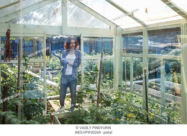 Smiling young woman standing in a greenhouse