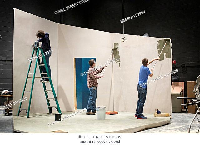 Students constructing theater set on stage