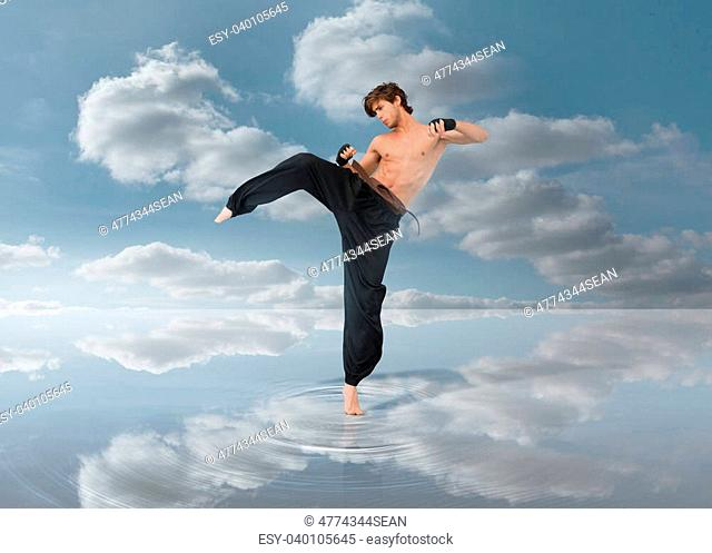 Martial arts fighter over puddle with the blue sky in background