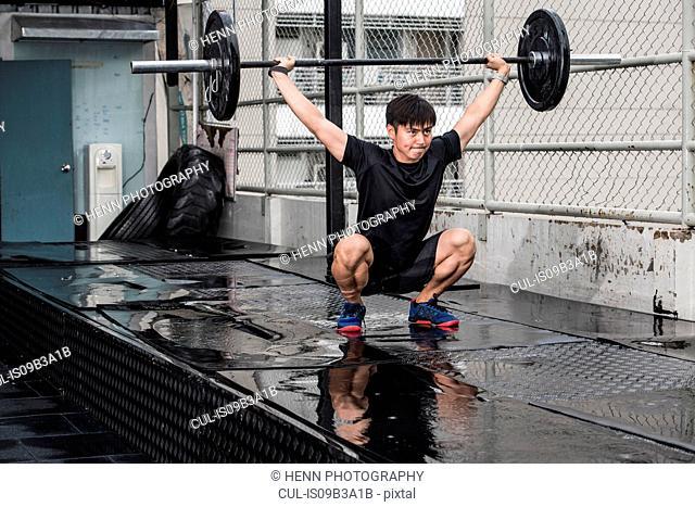 Man lifting barbell in rooftop gym, Asok, Bangkok, Thailand
