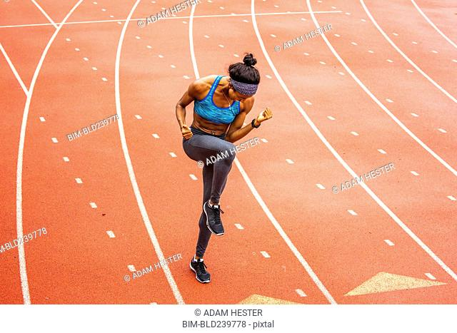 Happy Black athlete celebrating on track