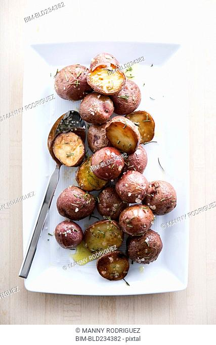 Spoon on plate of roasted potatoes