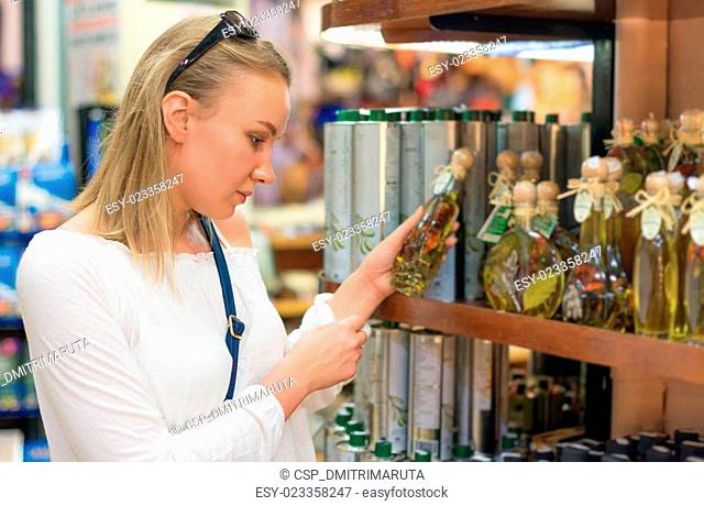 Young woman choosing olive oil in grocery store