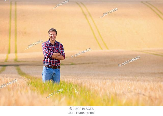 Portrait confident farmer standing in sunny rural barley crop field in summer