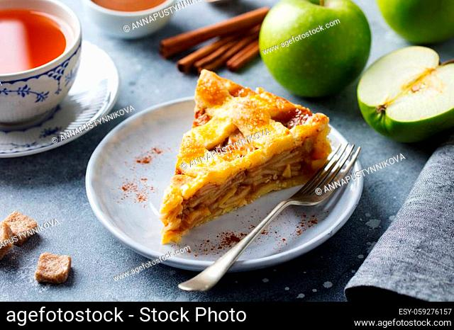 Apple pie on a white plate with a cup of tea. Breakfast time. Close up