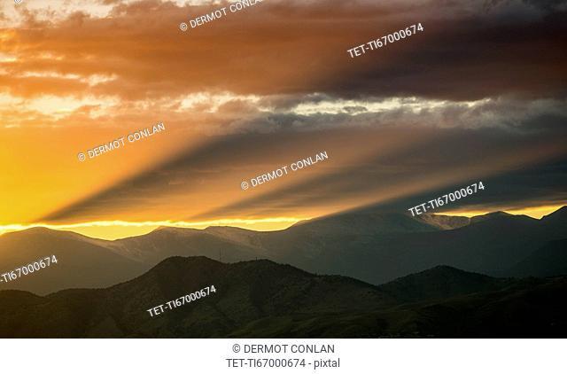 USA, Colorado, Denver, Setting sun shining through clouds over Front Range