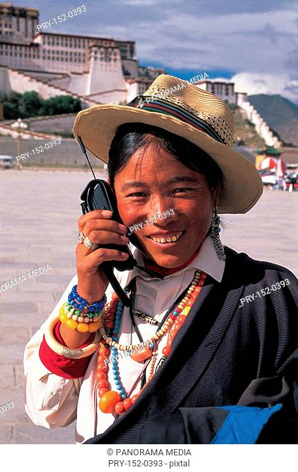 Tibet woman talking on cellphone in front of Potala Palace