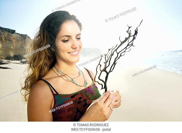 South Africa, smiling woman on the beach holding twig