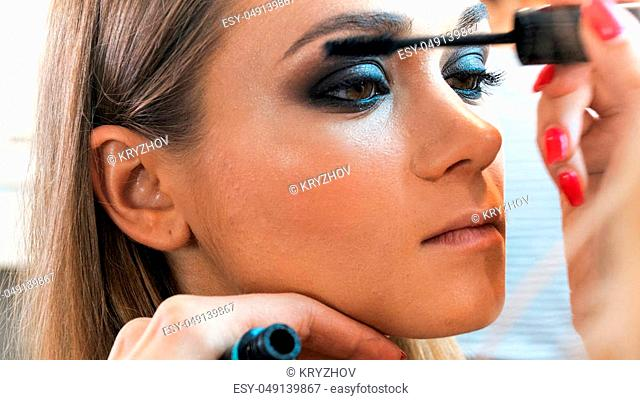 Image of Makeup artist painting young model's eyes with black mascara