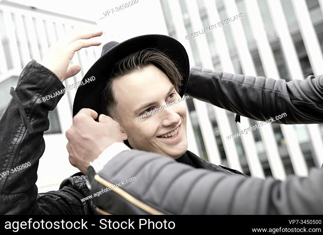 Man adjusting friend's hat. Munich, Germany