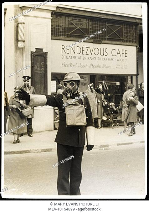 A traffic policeman on point duty carries on regardless, wearing his gas mask, during a tear-gas exercise outside the 'Rendezvous Cafe' in Kingston- upon-Thames