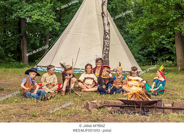 Germany, Saxony, Indians and cowboy party, Children sitting at bonfire