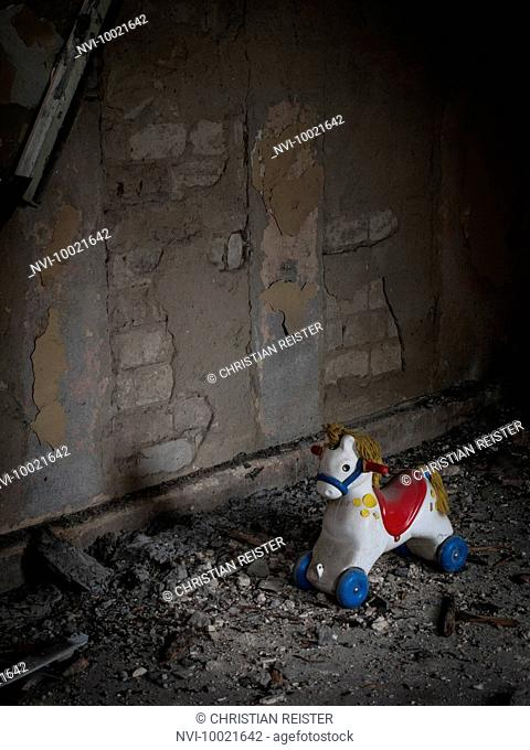 Toy horse in an old ruined house