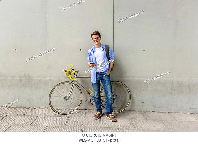 Smiling young man with racing cycle and cell phone in front of concrete wall