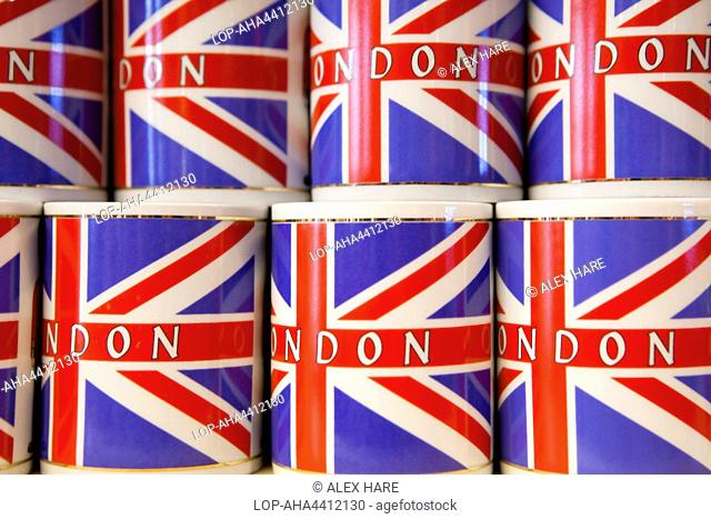 England, London. Mugs bearing a Union flag and the word 'London' stacked on a shop shelf