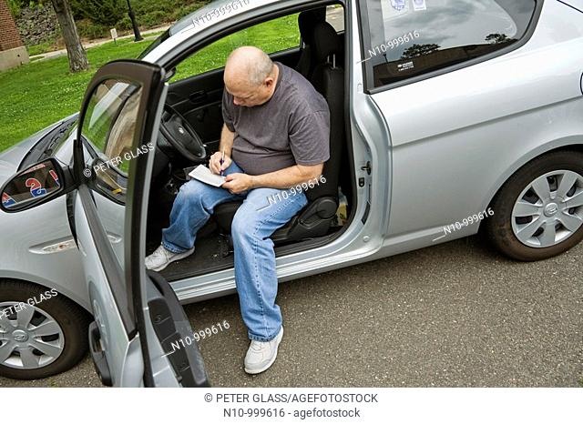 Man sitting in his car, filling out a form