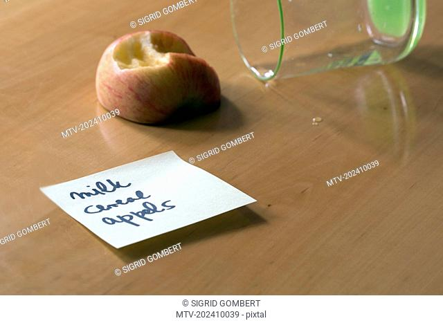 Close-up of adhesive note with apple and glass