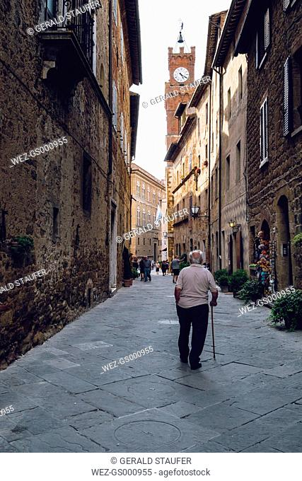 Italy, Tuscany, Pienza, Old man walking in historic old town