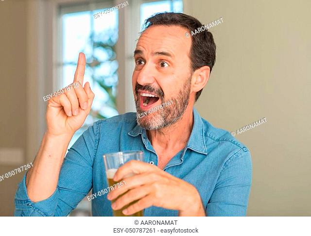 Middle age man drinking beer surprised with an idea or question pointing finger with happy face, number one
