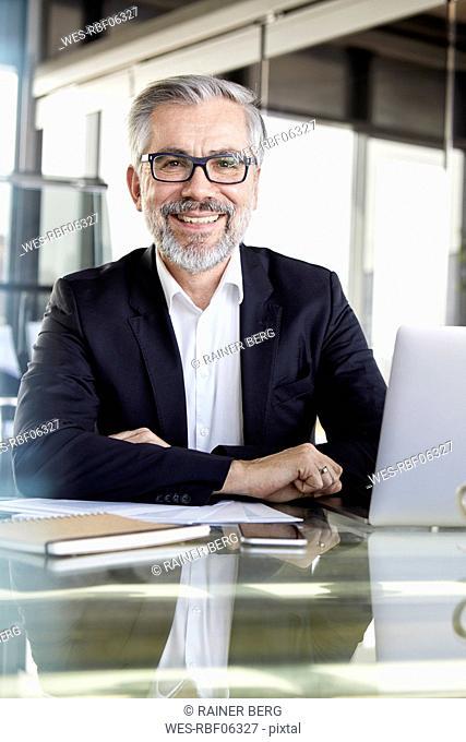Portrait of smiling businessman at desk in office