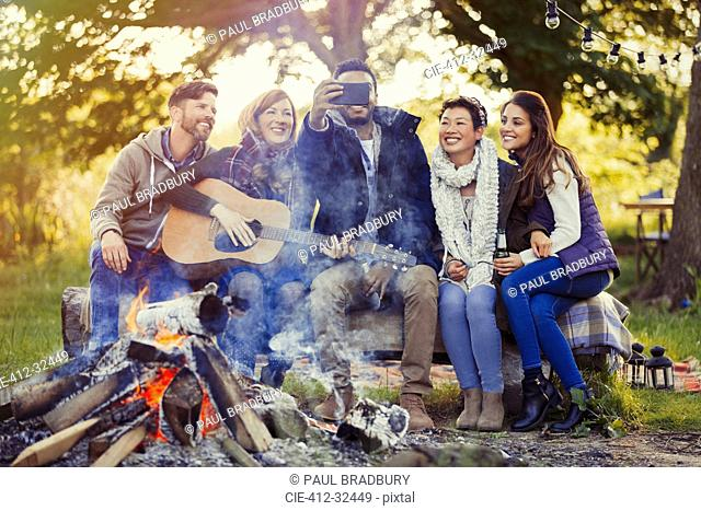 Smiling friends with camera phone taking selfie at campfire
