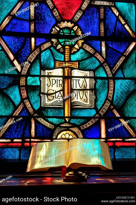 Colored light from stained glass window in methodist church falls across open bible