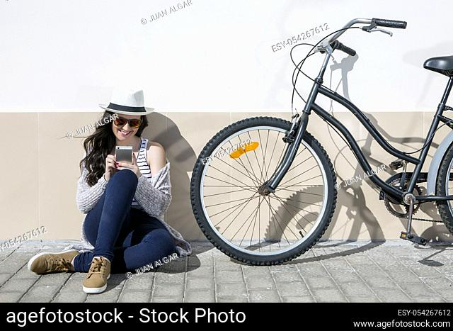 Young cheerful woman in sunglasses and hat sitting nearby bike and using device. Lanzarote, Gran Canaria, Spain