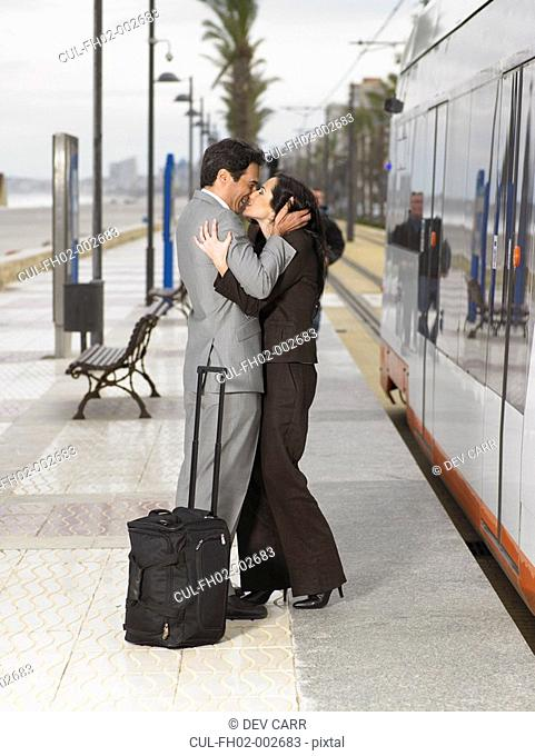 Couple wearing business suits kissing each other on platform next to static train/tram