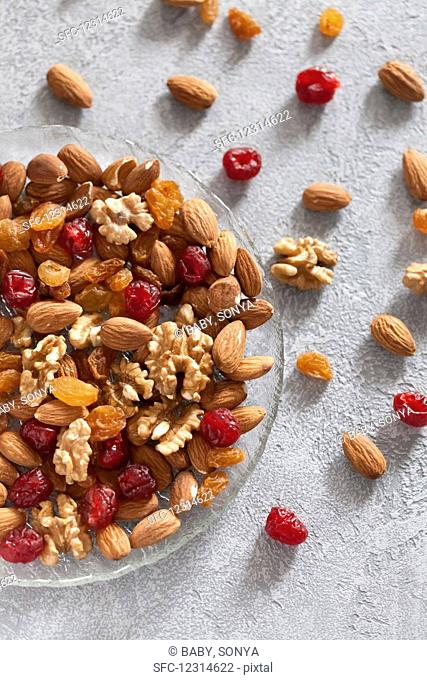 Nuts and dried fruits on the plate on the concrete surface