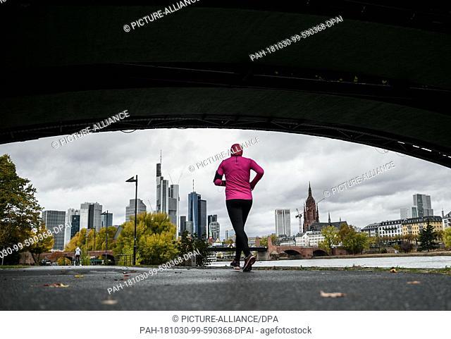 30 October 2018, Hessen, Frankfurt/Main: A female jogger runs under the Ignatz-Bubis-Bridge on the Frankfurt Main bank towards the skyline in autumn weather