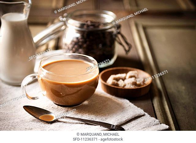 Milky coffee in a glass cup; coffee beans in the background