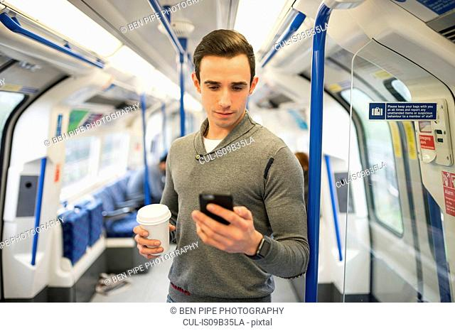 Man on train looking at smartphone