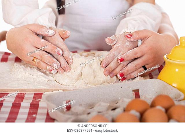 Caring Hands mother helping her daughter prepare dough