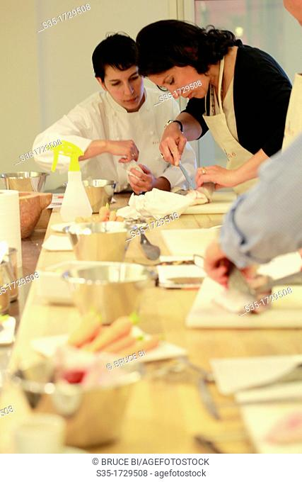 Alain Ducasee trained chef Sabrina Zoli helping her students in the cooking class in Ecole de Cuisine Alain Ducasse (Alain Ducasse cooking school), Paris