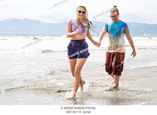 Beach scene with young woman and man walking, Riviera Nayarit, Pacific Coast, Mexico