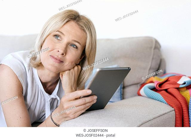 Portrait of mature woman lying on couch at home holding tablet