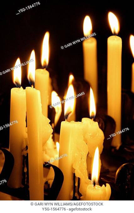 many lit candles in dark room in church