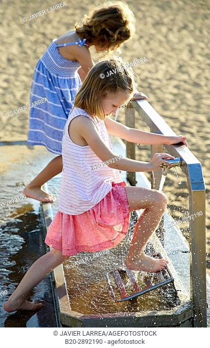 Girls wiping their feet on the beach, Zarautz, Gipuzkoa, Basque Country, Spain, Europe