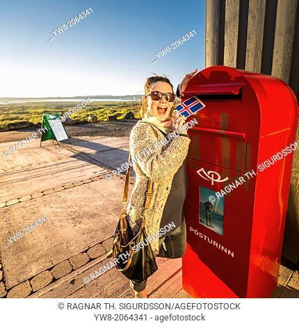 Woman mailing a postcard from Dimmuborgir, Northern Iceland