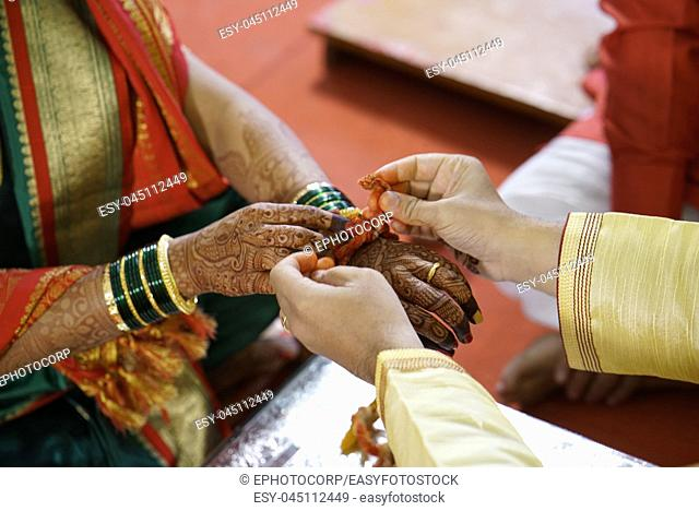 Traditional Hindu marriage ceremony where groom tides holy thread on the wrist of bride