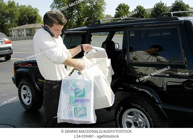 Young white male loaded down with shopping packages uses cell phone