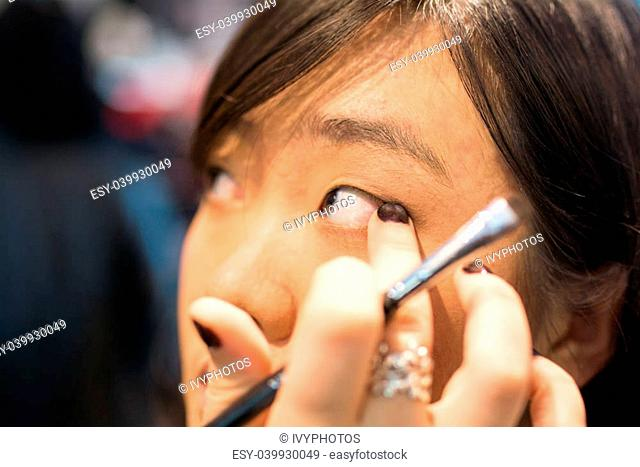 Young Asian woman applying eye liner with a small brush