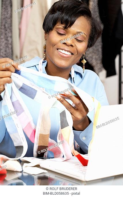 African fashion designer holding fabric swatches