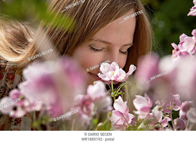 Mid adult woman smelling flowers, Munich, Bavaria, Germany