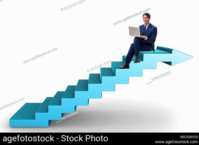 Businessman in career ladder concept working on laptop