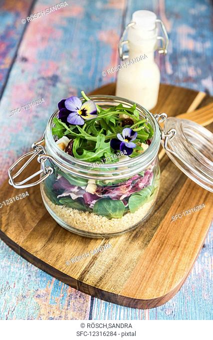 A quinoa salad with lambs lettuce, radicchio, rocket, croutons, goat's cheese and horned violets in a glass jar on a wooden board