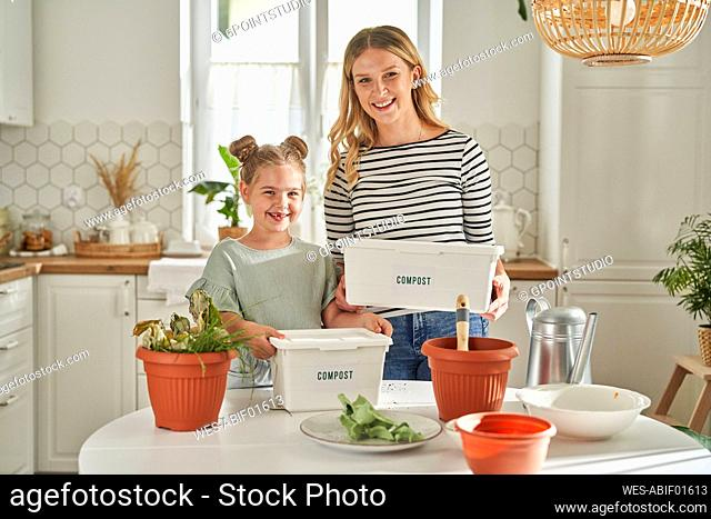 Happy mother and daughter holding homemade compost containers in kitchen