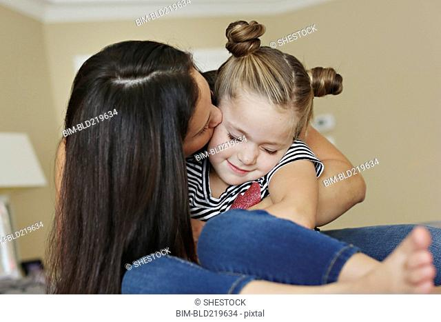 Close up of mother kissing cheek of daughter