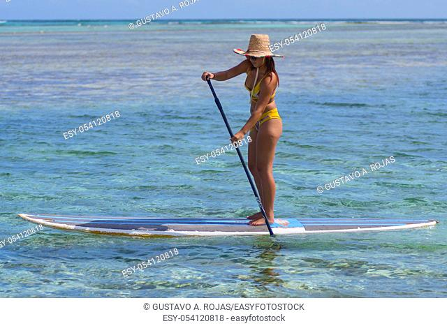 young woman practising paddle board or sup in tropical Caribbean sapphire crystal clear calm waters