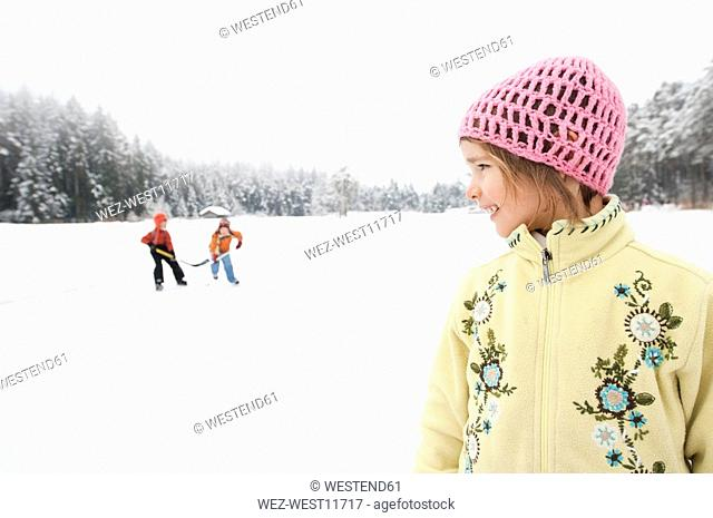 Italy, South Tyrol, Seiseralm, Two Boys playing ice hockey, girl 4-5 in foreground, portrait
